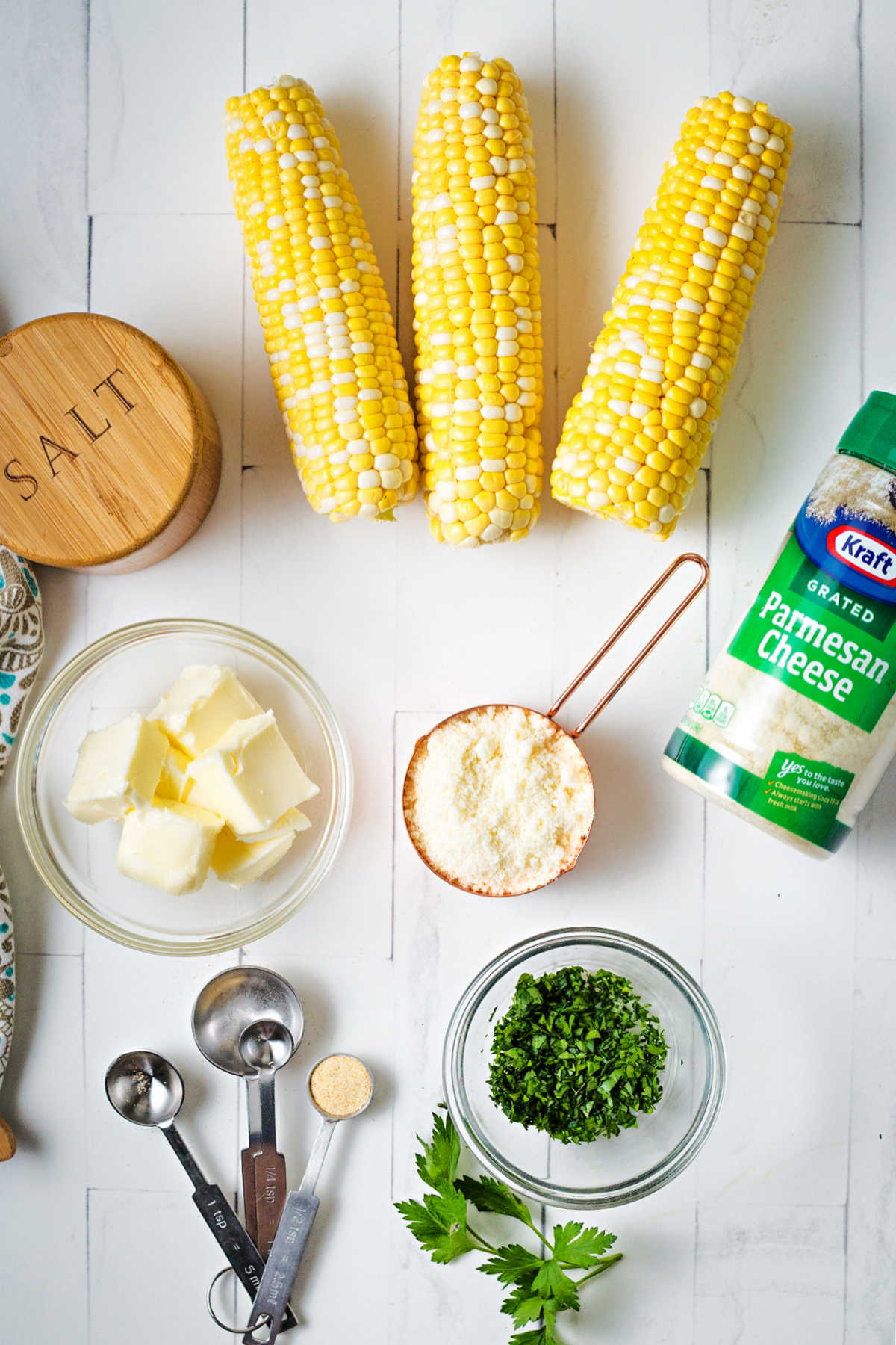 ingredients for grilled corn on a table: fresh ears of corn, softened butter, grated parmesan cheese, and freshly chopped parsley.