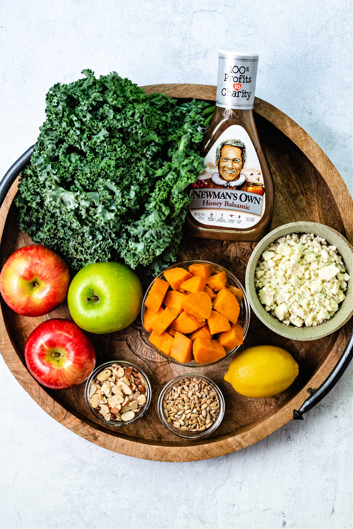 ingredients for harvest chicken salad on a wooden tray: a bunch of curly kale, apples, blue cheese crumbles, balsamic dressing, a lemon, sunflower seeds, a bowl of sweet potato chunks, and almonds.