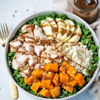 harvest chicken salad in a bowl drizzled with balsamic vinaigrette.