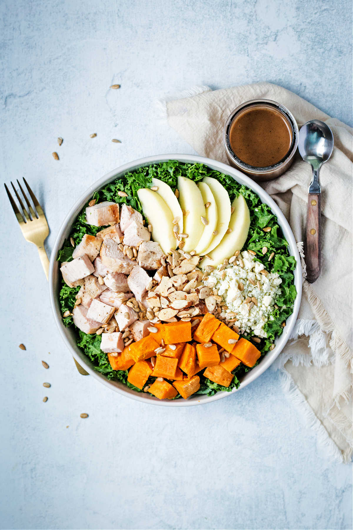 a salad bowl on a table top filled with chopped kale, sweet potatoes, blue cheese, apples, and chicken with a side of balsamic dressing.