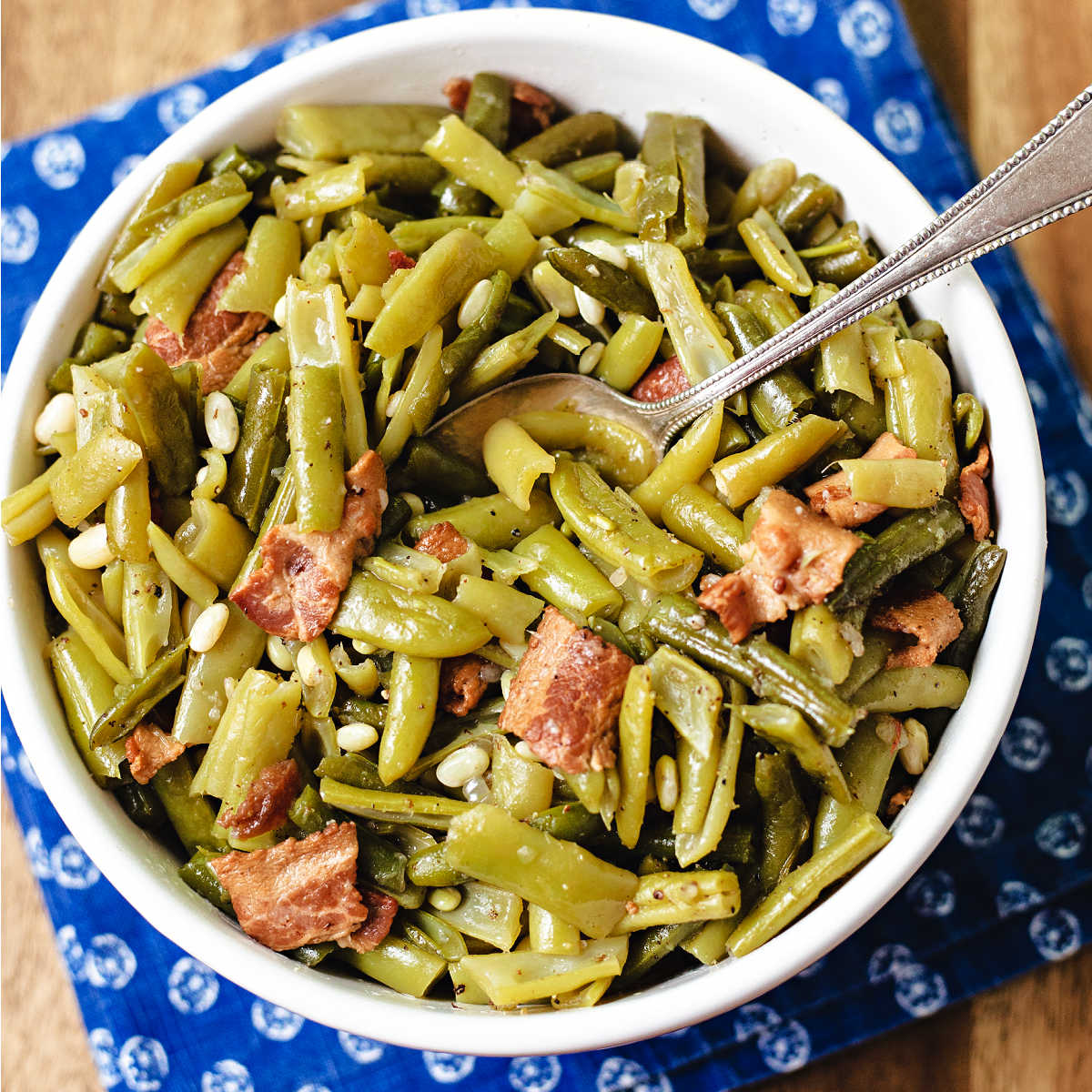 a bowl of green beans with a serving spoon sitting on a blue napkin on a wooden table.