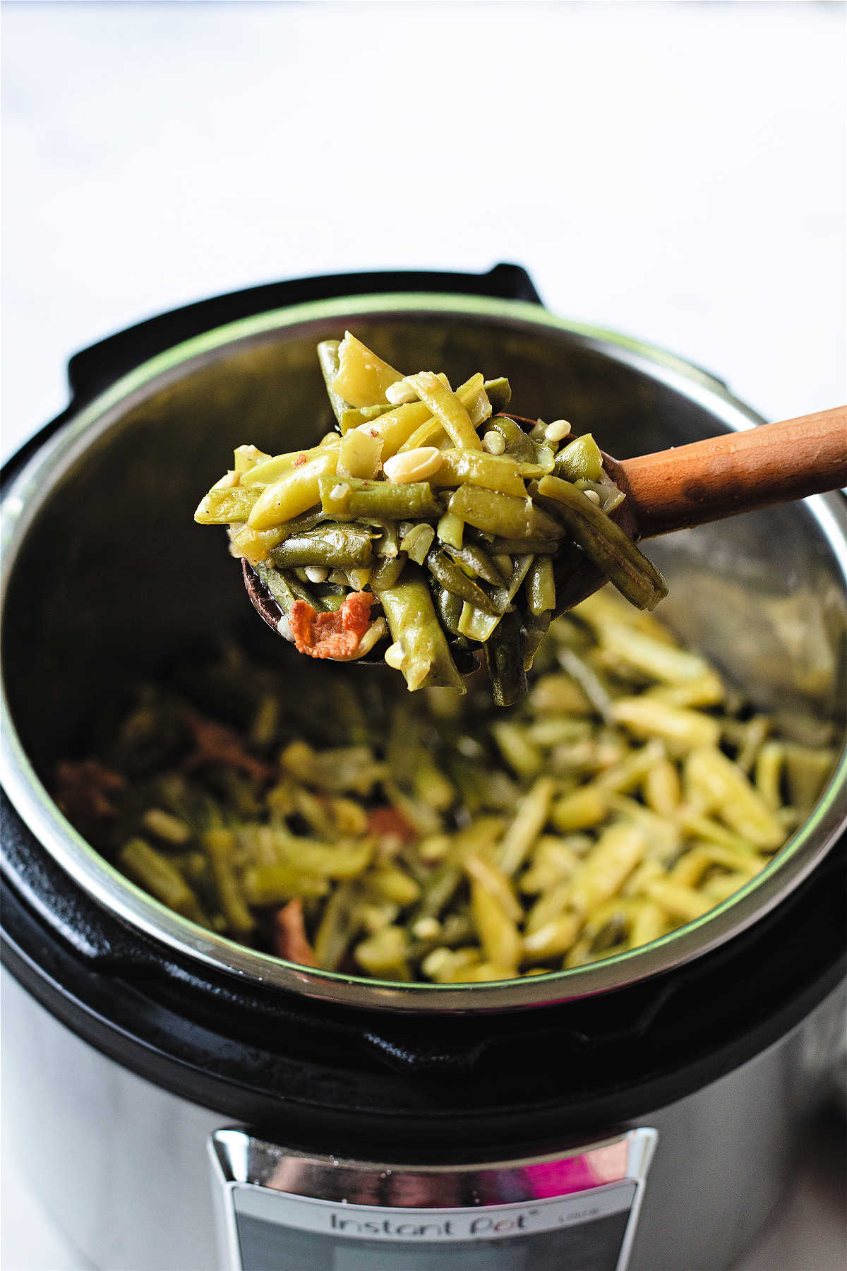 a wooden spoon lifting green beans out of an instant pot.