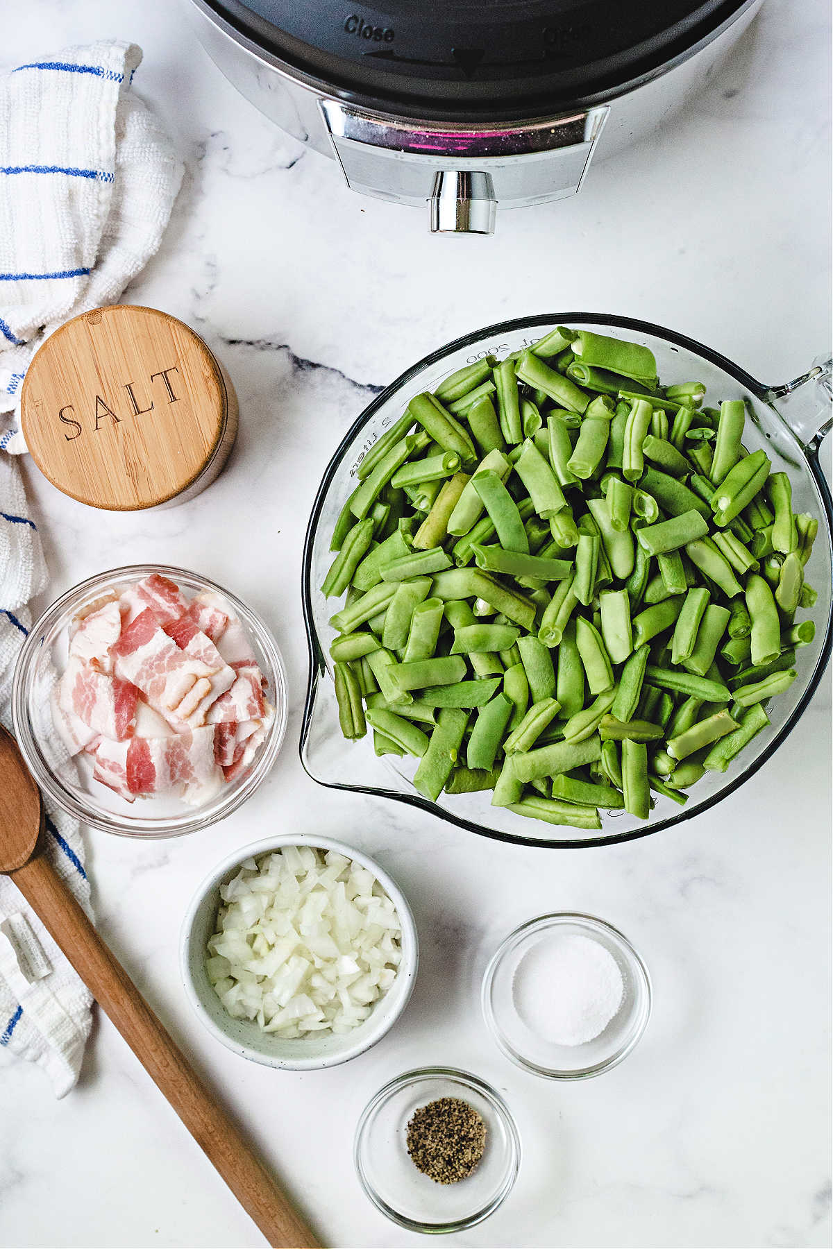 ingredients for cooking green beans in an instant pot on a kitchen counter: fresh green beans, bacon, diced onion, salt, pepper, and sugar.