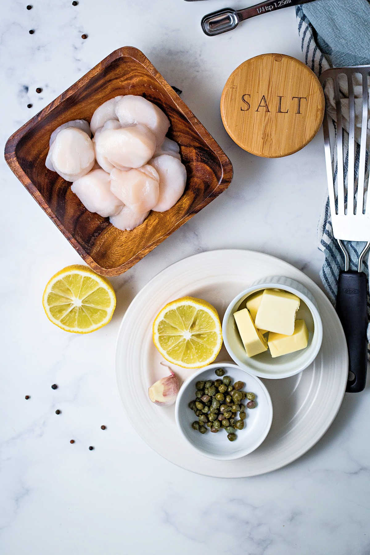 ingredients for making seared scallops on a counter: raw scallops, lemon, capers, butter, and salt.