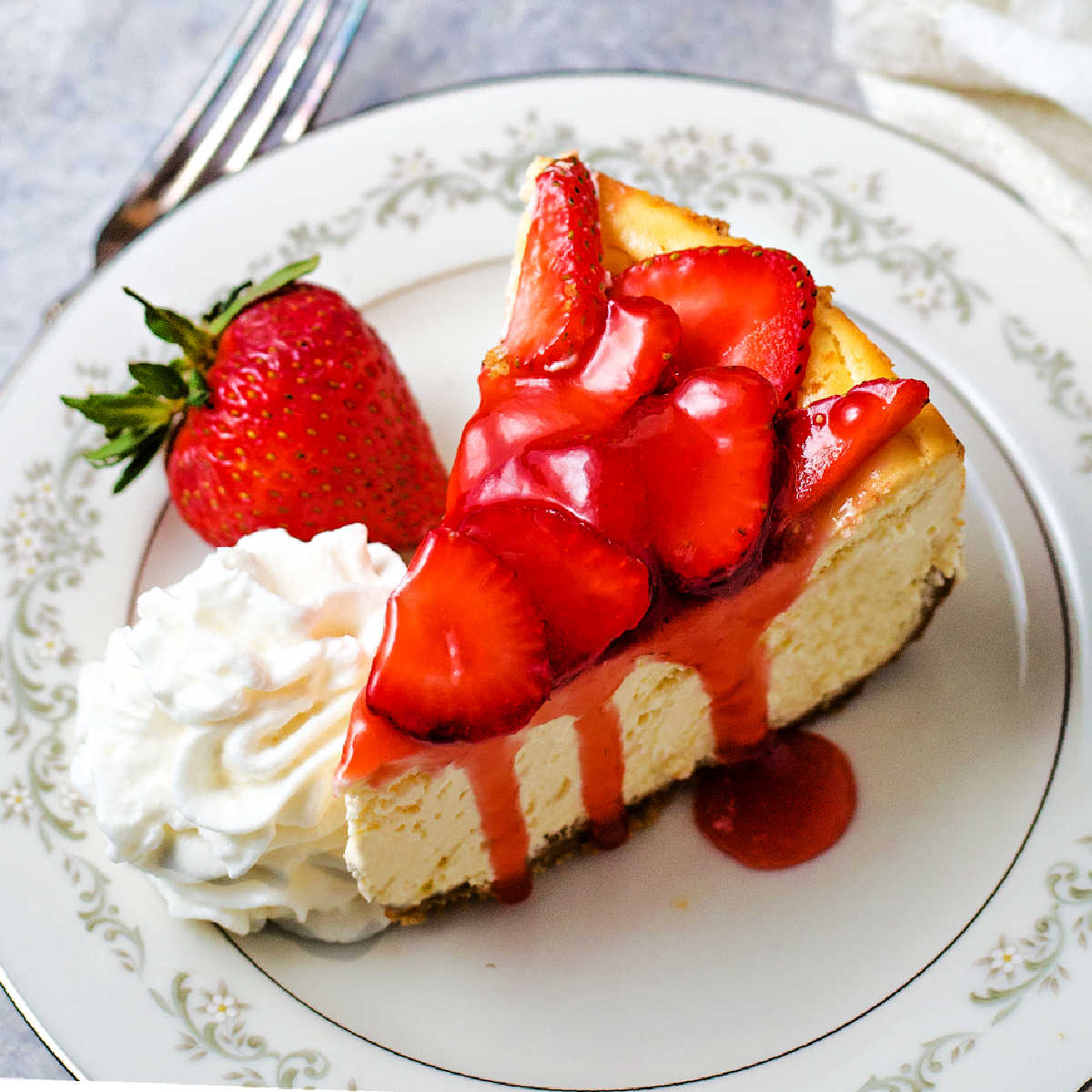 a slice of strawberry cheesecake on a china plate with a mound of whipped cream on the side.