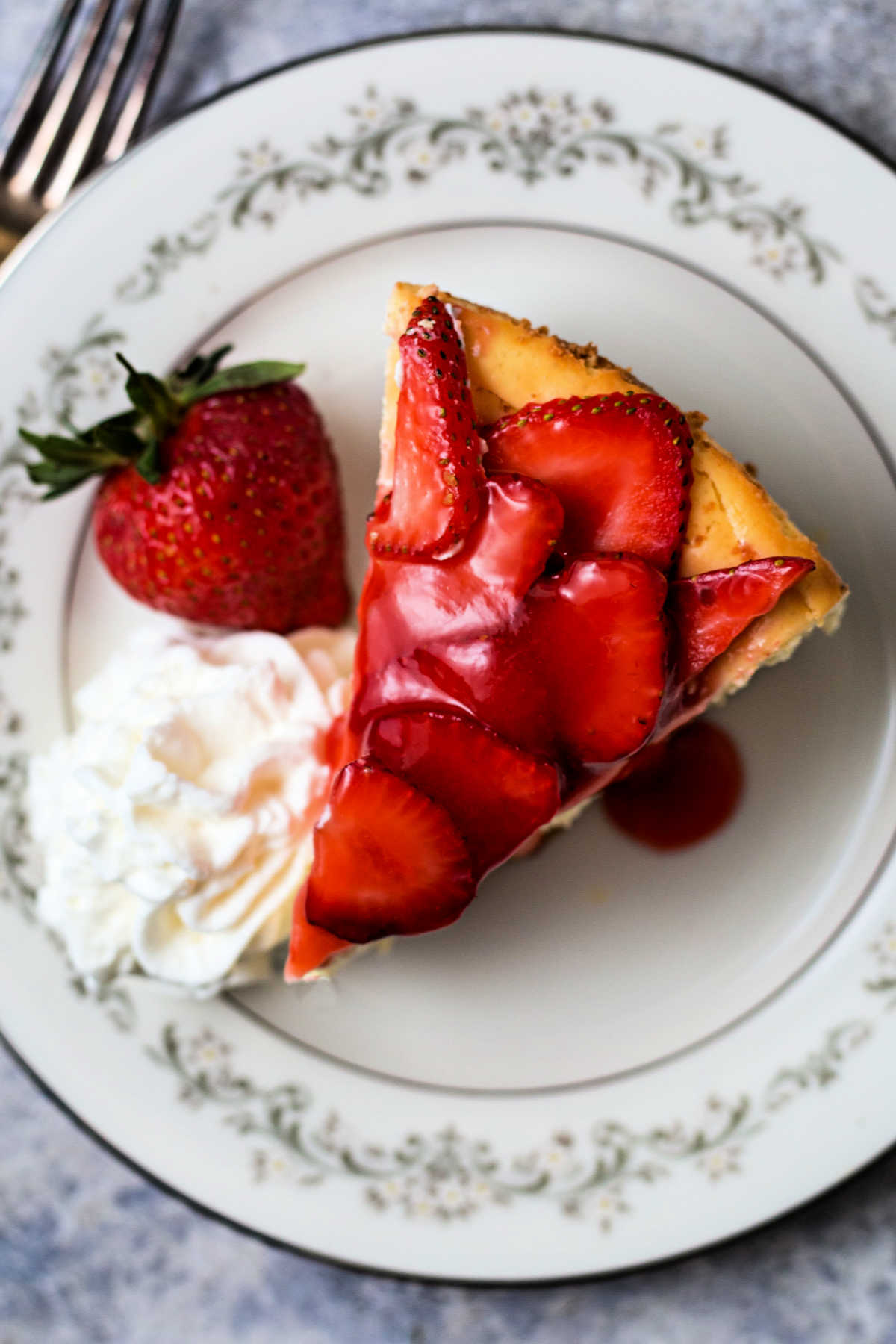 top down view of a slice of strawberry cheesecake on a china plate with a mound of whipped cream on the side.
