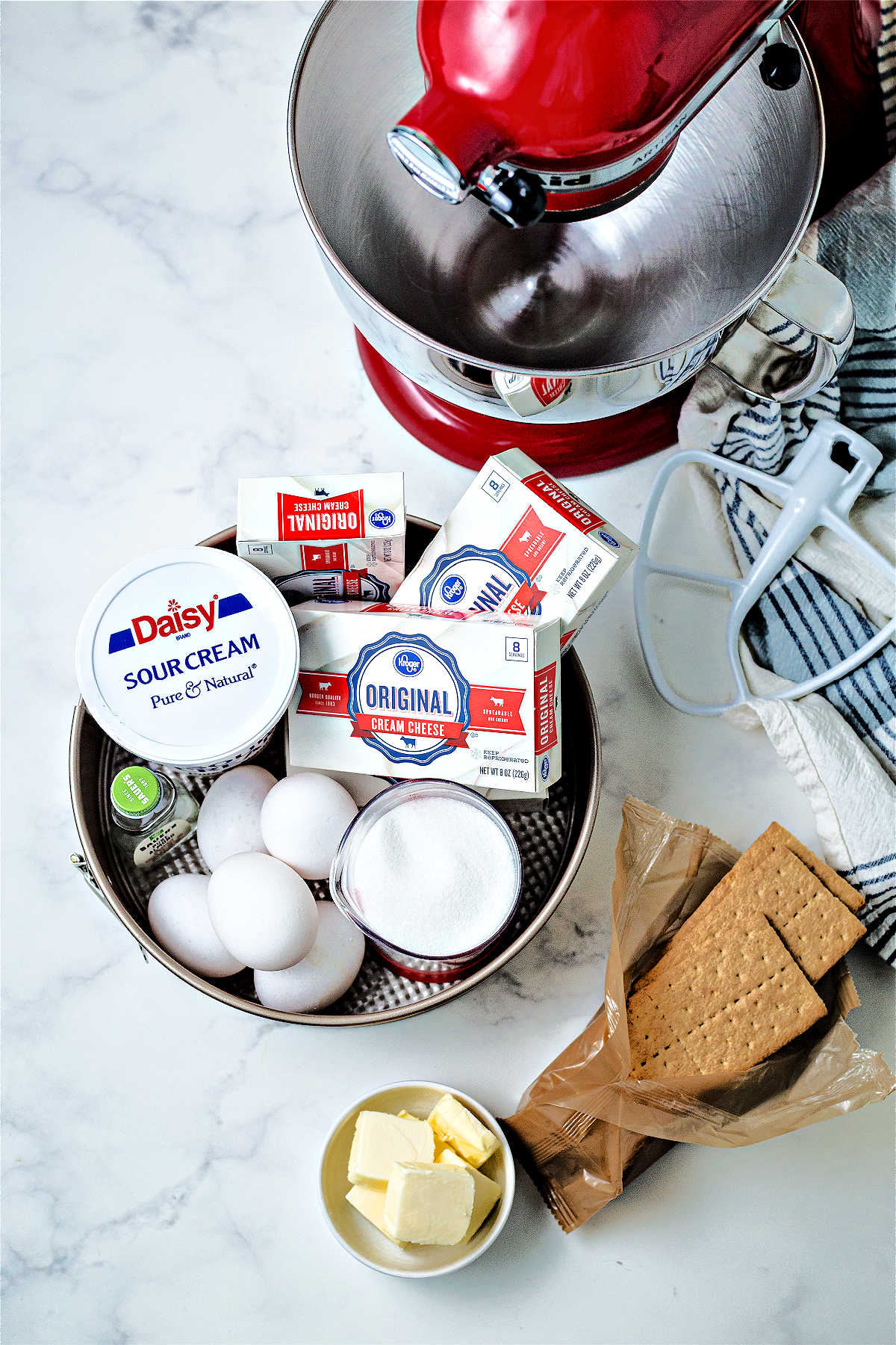 ingredients for strawberry cheesecake on a counter with a stand mixer and springform pan.