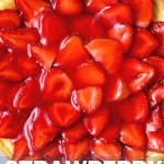top down view of a whole strawberry cheesecake with strawberries arranged in a decorative pattern.