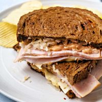 a turkey reuben sandwich cut in half and stacked on top of each other on a white plate with potato chips.