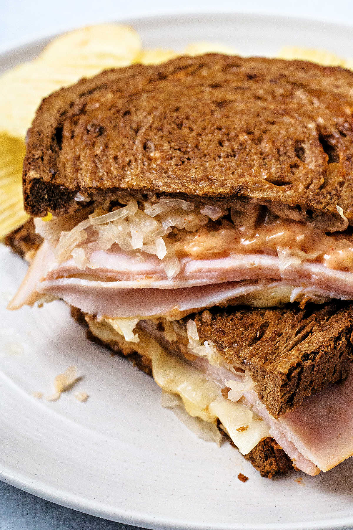 close up of a turkey reuben sandwich cut in half and stacked on top of each other on a white plate with potato chips.