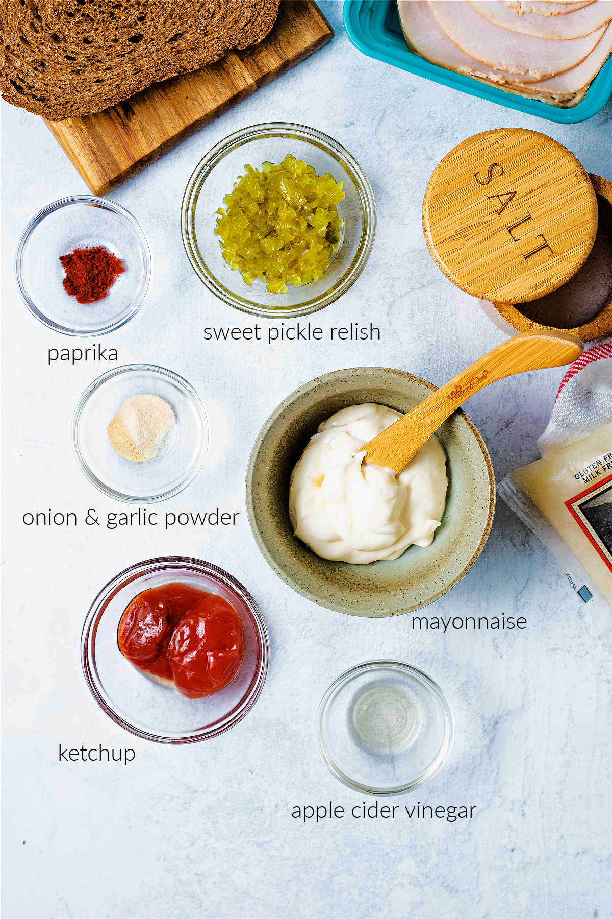 ingredients for thousand island dressing on a kitchen counter: mayonnaise, ketchup, pickle relish, cider vinegar, and seasonings.
