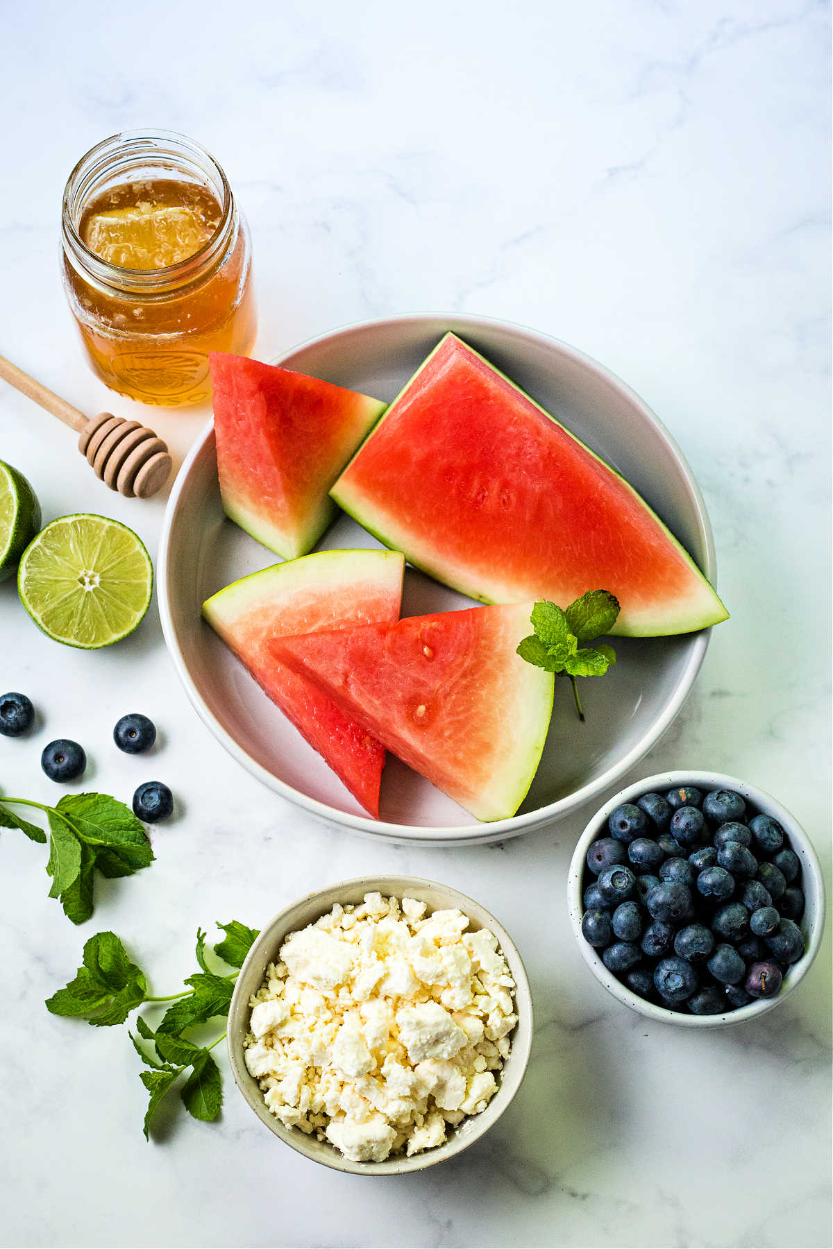 ingredients for watermelon and feta salad on a counter top: wedges of watermelon in a plate; feta cheese; blueberries; fresh mint sprigs; a jar of honey and a lime.