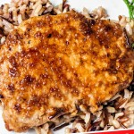 Balsamic Pork Chops on a bed of wild rice on a while platter.