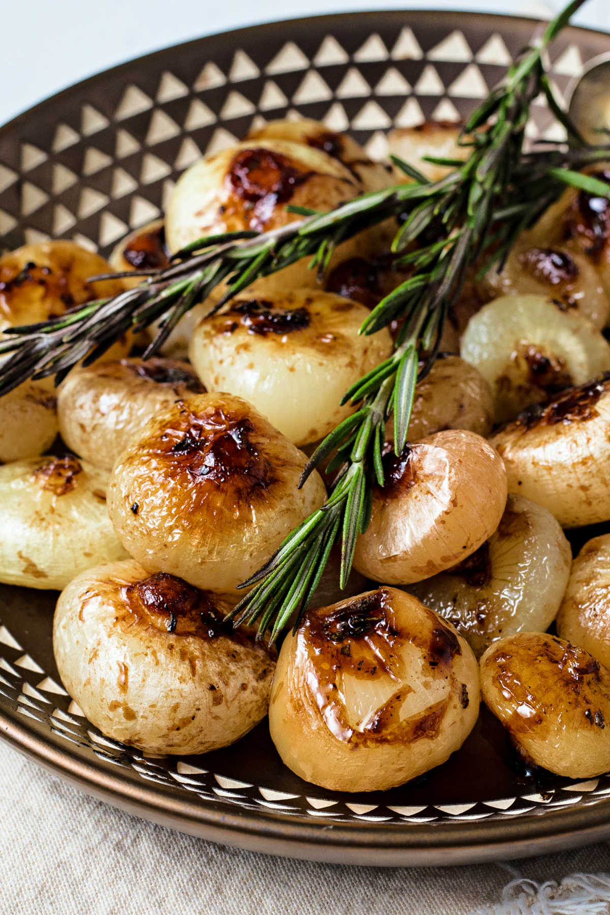 a copper bowl of balsamic glazed cipollini onions garnished with rosemary.