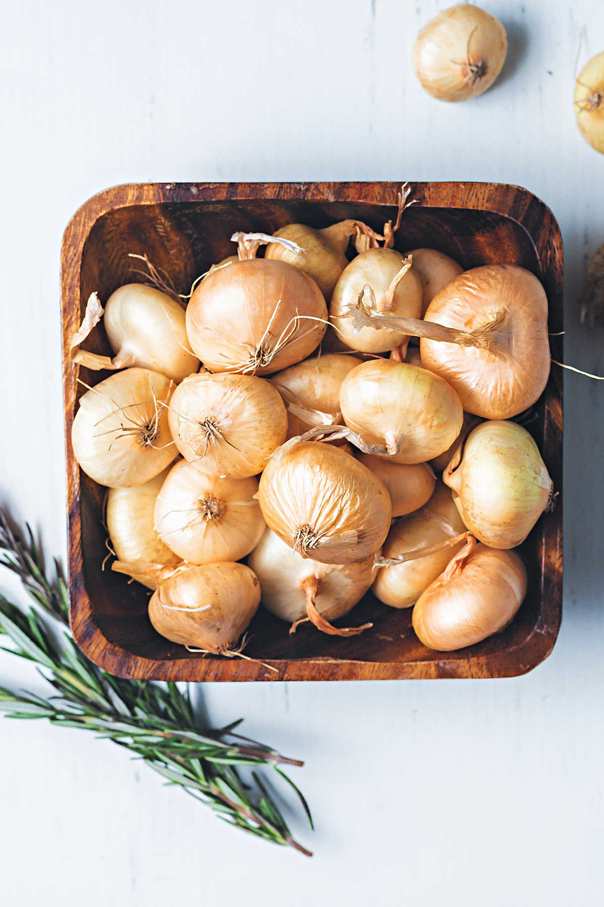 a wooden bowl on a table filled with uncooked cipolline onions.