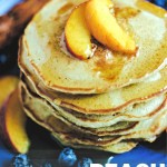 a stack of peach pancakes with sliced peaches on top and drizzled with maple syrup on a blue plate.