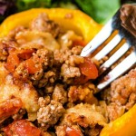a yellow bell pepper stuffed with saucy turkey mixture on a plate with a side salad.