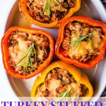 four saucy turkey stuffed peppers in a white baking dish on a table.