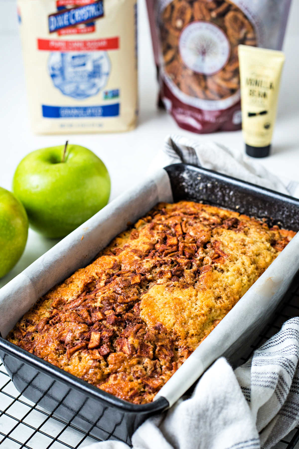 apple cinnamon bread in a loaf pan cooling on a wire rack with apples in the background.