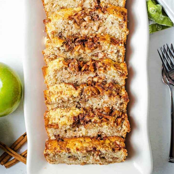 slices of apple cinnamon bread on a white platter on a table.
