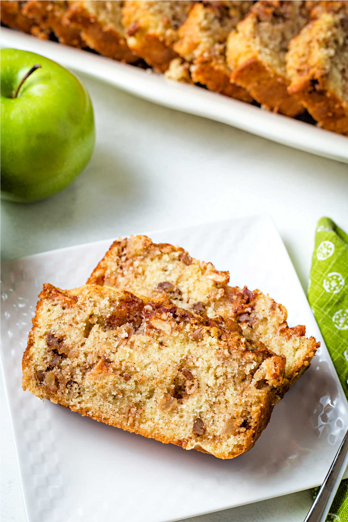 two slices of apple cinnamon bread on a square white plate with a Granny Smith apple in the background.