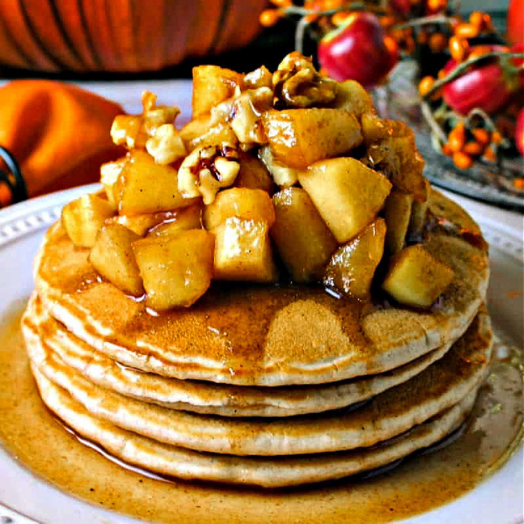 a stack of cinnamon pancakes topped with apple compote and walnuts on a white plate with autumn decor in the background.