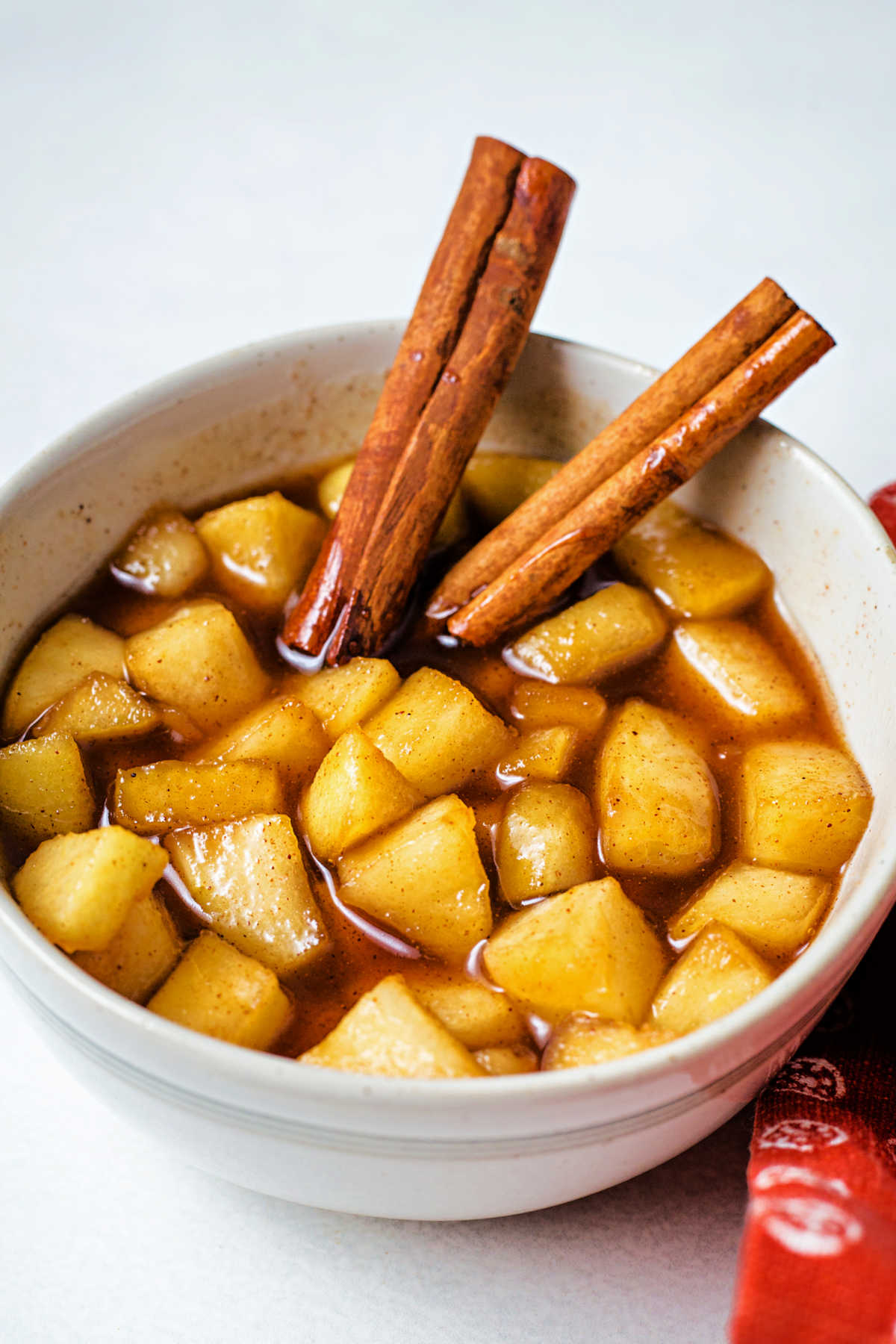 a bowl of apple compote with cinnamon sticks.