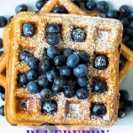 blueberry waffles stacked on top of each other and dusted with powdered sugar and sprinkled with blueberries.