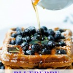 syrup being poured over a stack of blueberry waffles.