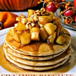 CINNAMON PANCAKES WITH APPLE COMPOTE ON A WHITE PLATE IN FRONT OF A FALL TABLESCAPE.