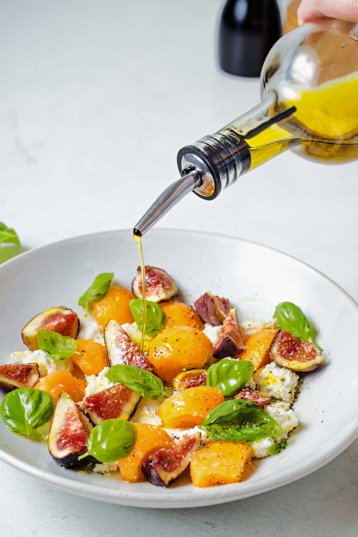 drizzling olive oil into a bowl of fig salad.