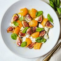fig salad with fresh mozzarella and cantaloupe in a shallow white bowl on a table.