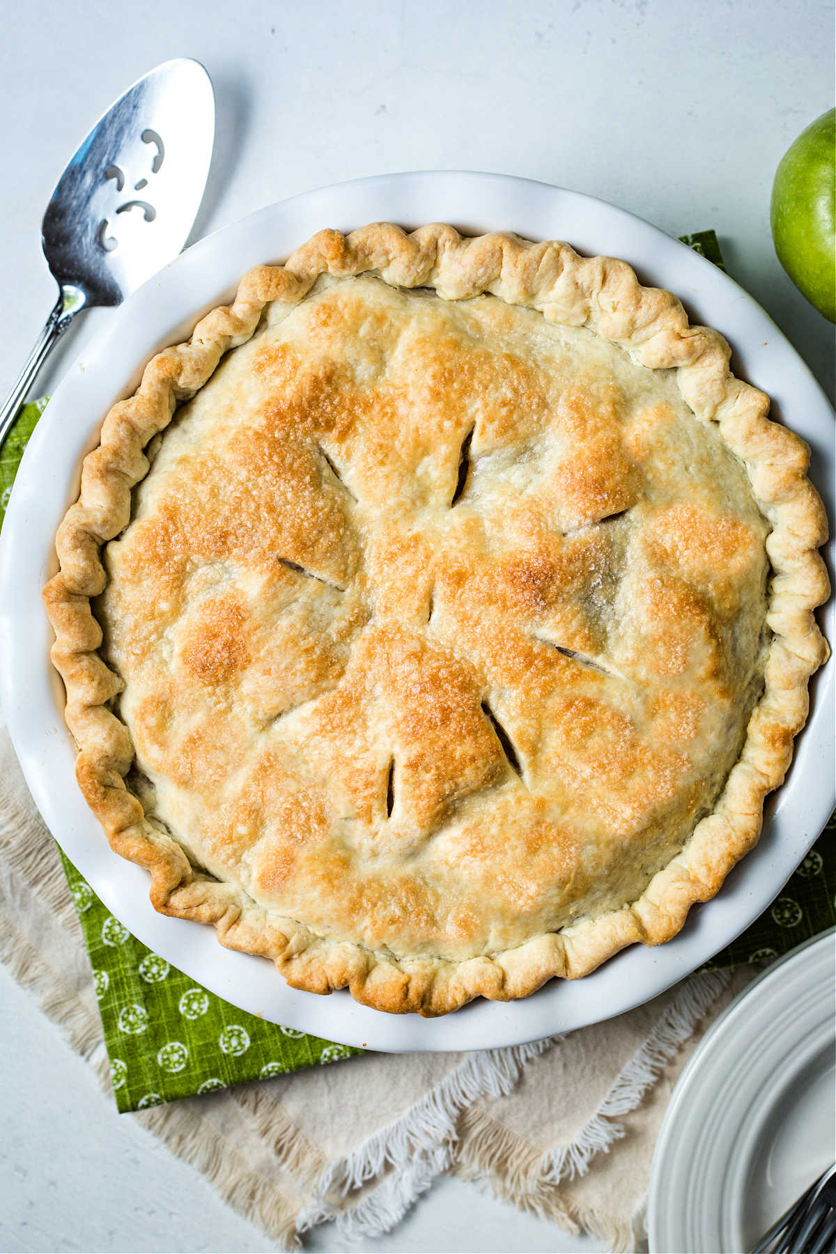 a whole baked apple pie in a white pie dish on top of a green and linen napkin with a pie server on a table.