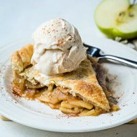 a slice of apple pie on a white plate with a scoop of vanilla ice cream and sprinkled with cinnamon.