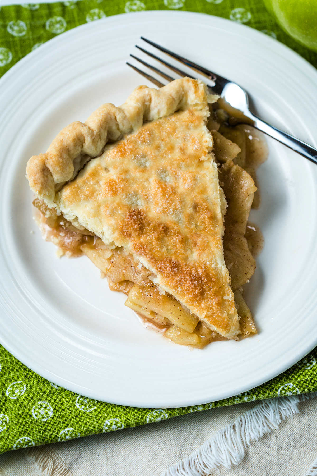 top down view of a slice of apple pie on a white plate with a fork on top of a green napkin.