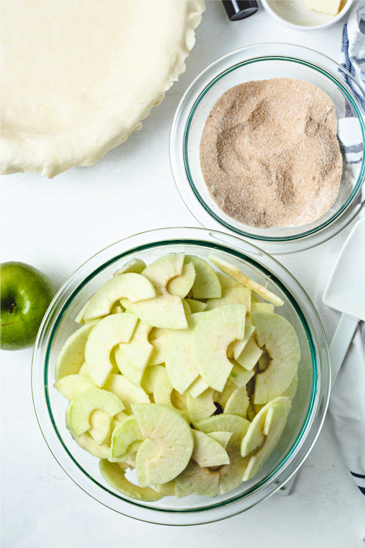 a bowl of thinly sliced apples, a bowl of cinnamon sugar, and an unbaked pie crust on a table.