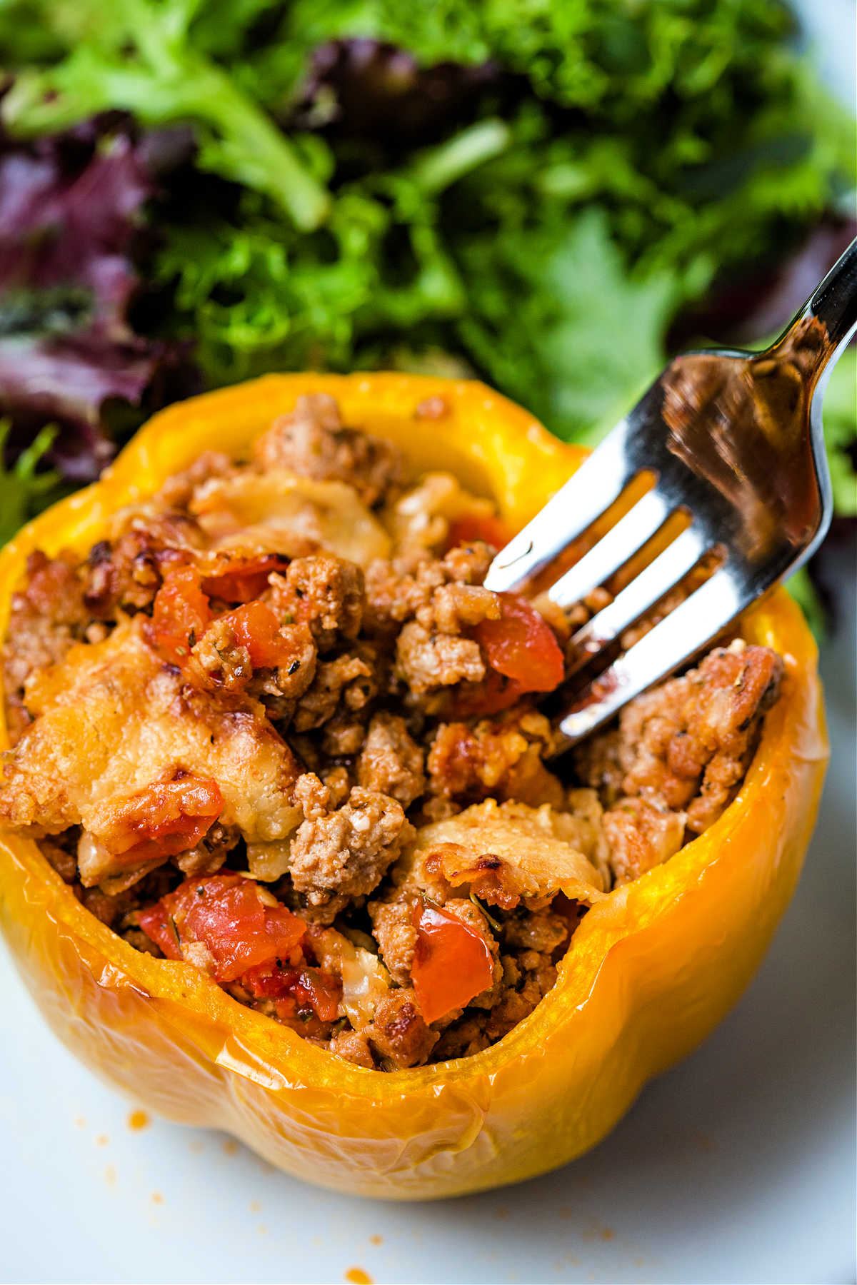 a fork spearing a bite from a yellow bell pepper stuffed with saucy turkey mixture on a plate with a side salad.
