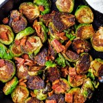 Caramelized brussels sprouts with bacon pieces in a cast iron skillet.