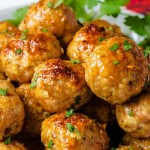 side view of a plate of chicken meatballs garnished with parsley on top of a red napkin on a table.