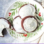 frosted chocolate drop cookies on a holiday plate with a glass of milk in the background.