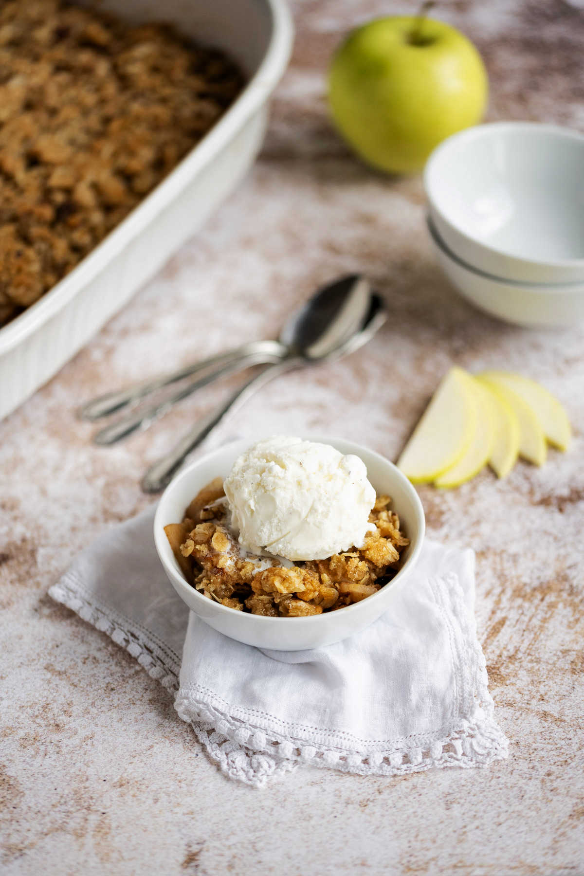 apple crisp in a white bowl with a scoop of vanilla ice cream on top sitting on a counter with apple and baking dish in the background.