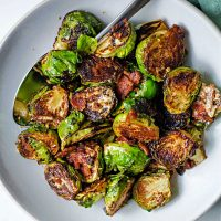 caramelized brussels sprouts in a white serving bowl with a spoon on a table.
