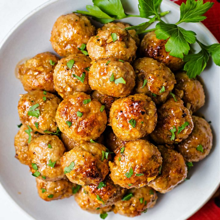 close up of a plate of chicken meatballs garnished with parsley on top of a red napkin on a table.