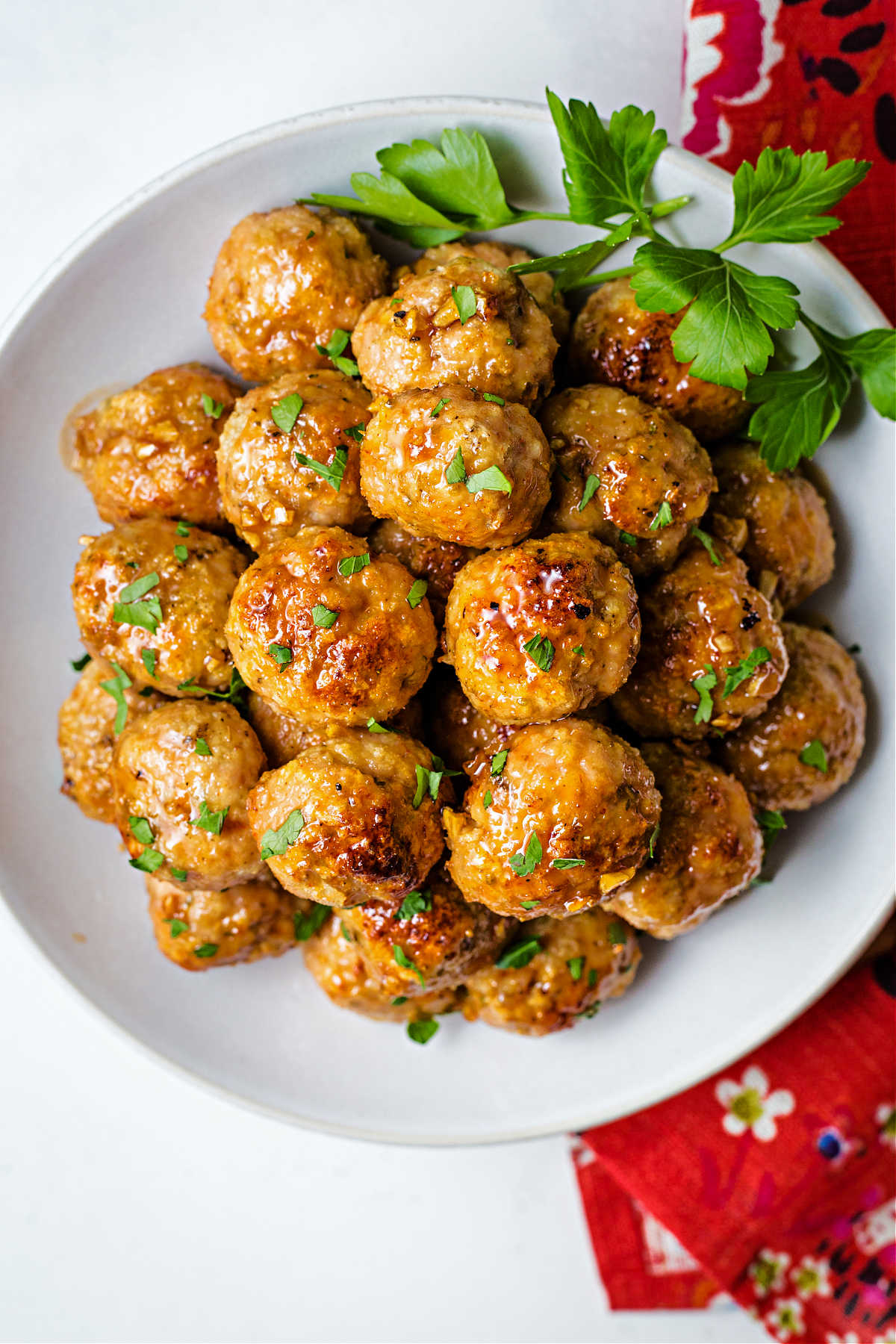 a plate of chicken meatballs garnished with parsley on top of a red napkin on a table.