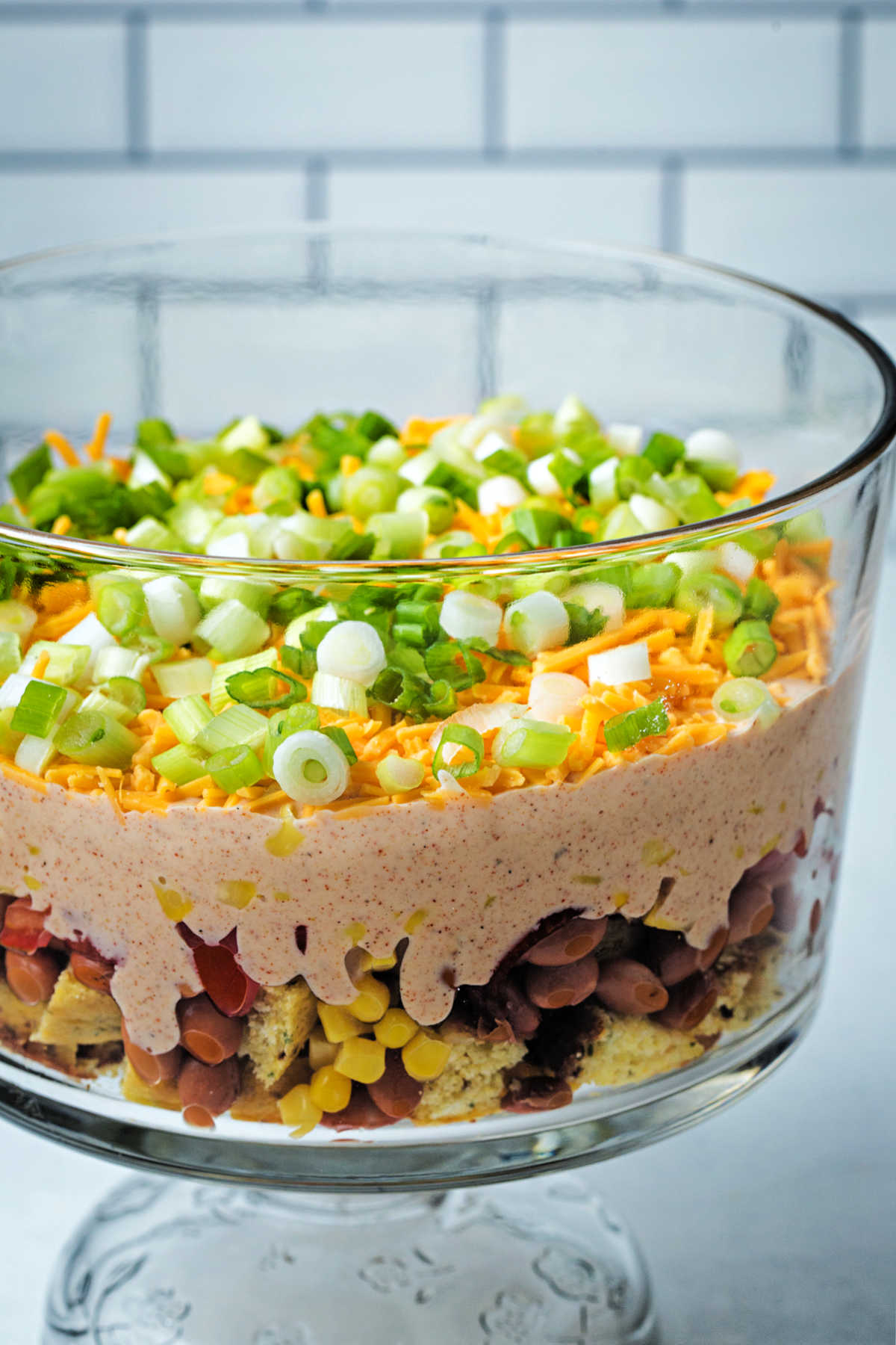 seven layer cornbread salad in a glass trifle bowl on a kitchen counter.
