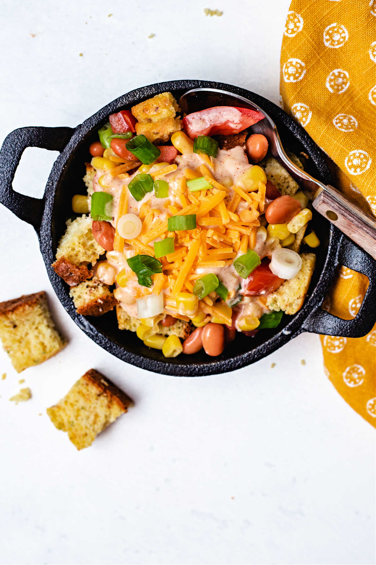 top down view of a serving of cornbread salad in a mini cast iron skilled with a spoon and yellow napkin on a table.