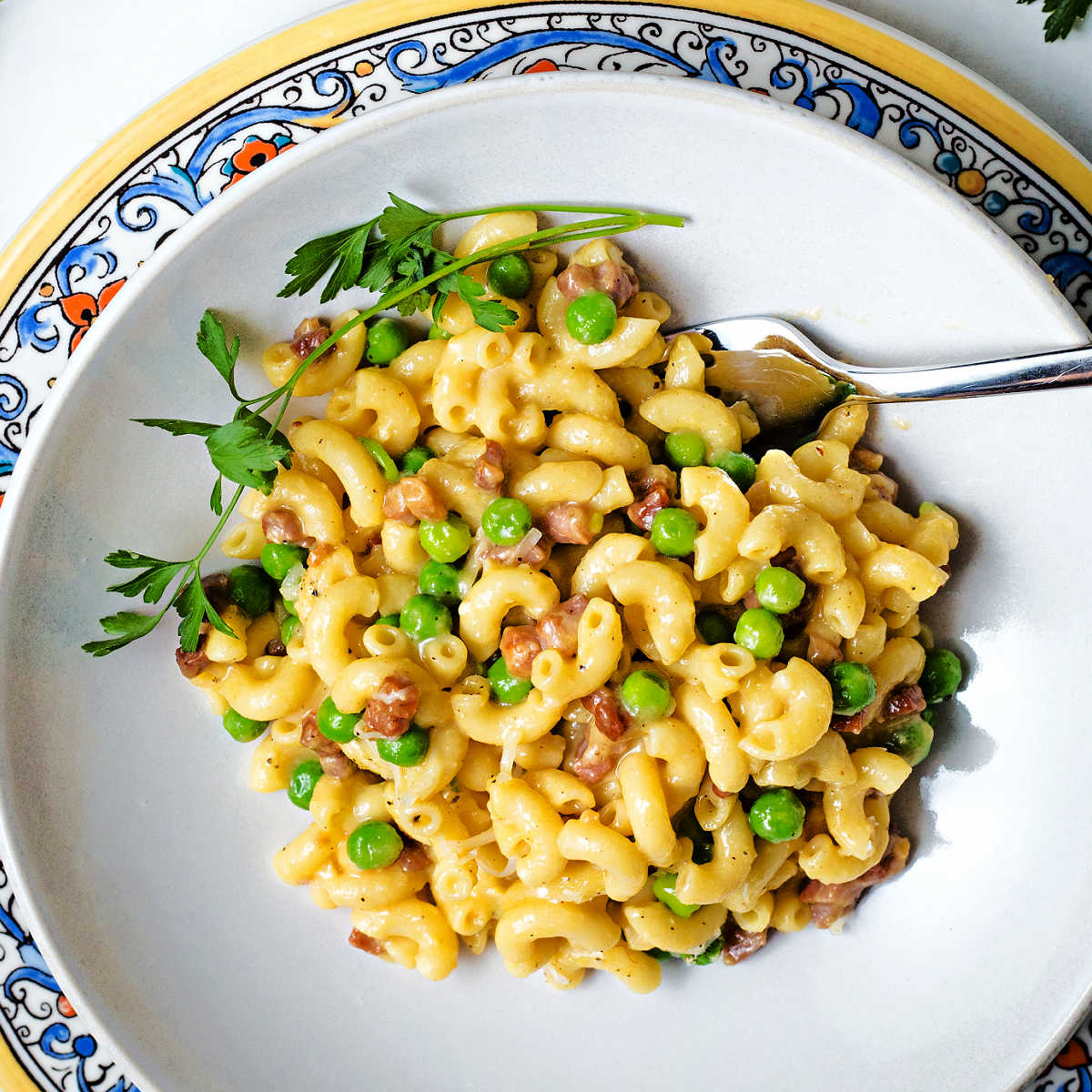 macaroni carbonara with prosciutto and green peas in a white bowl with a parsley garnish.