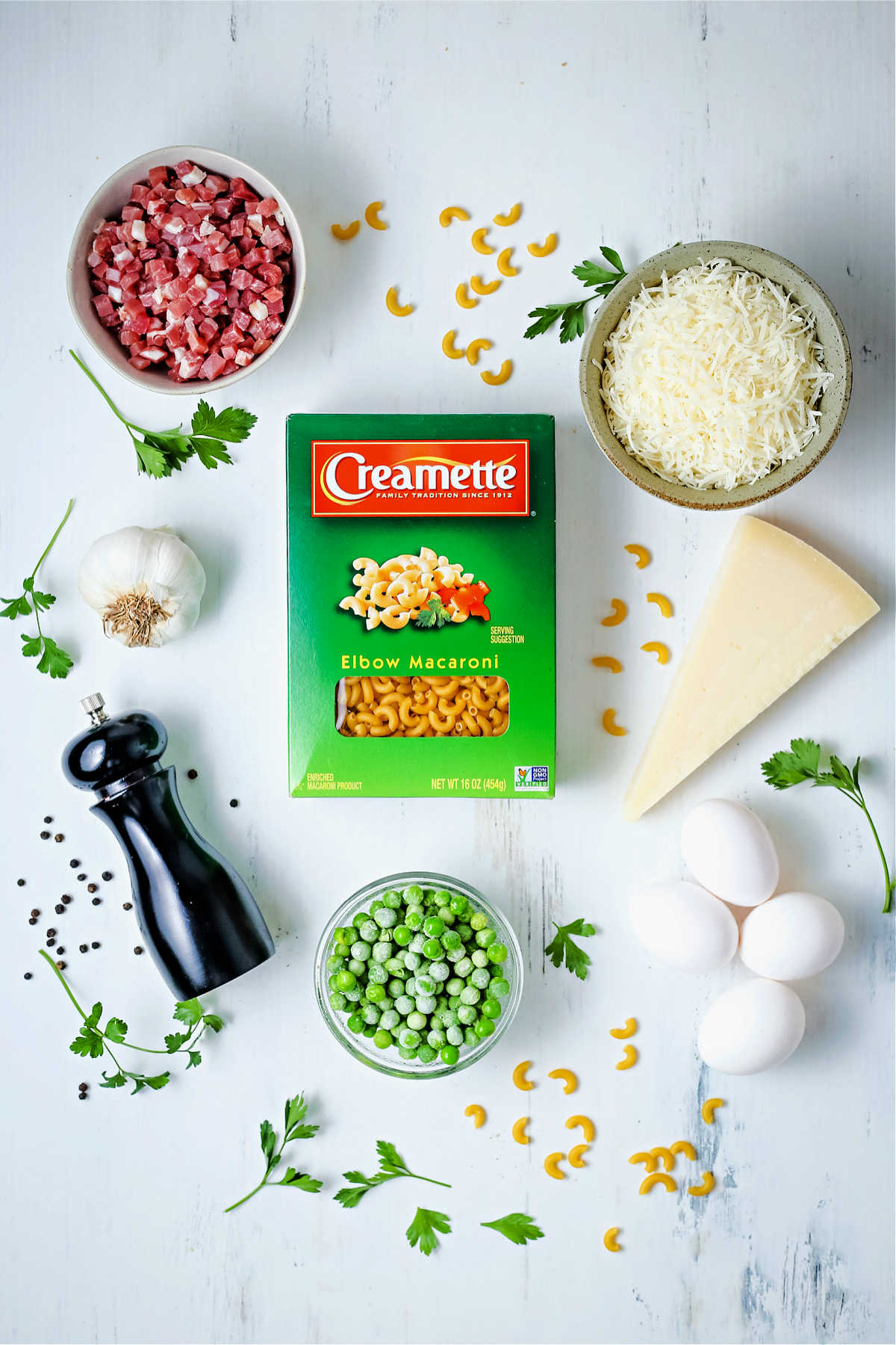 ingredients for preparing macaroni carbonara on a table: creamette elbow macaroni, cubed proscuitto, shredded parmesan cheese, frozen peas, and eggs.