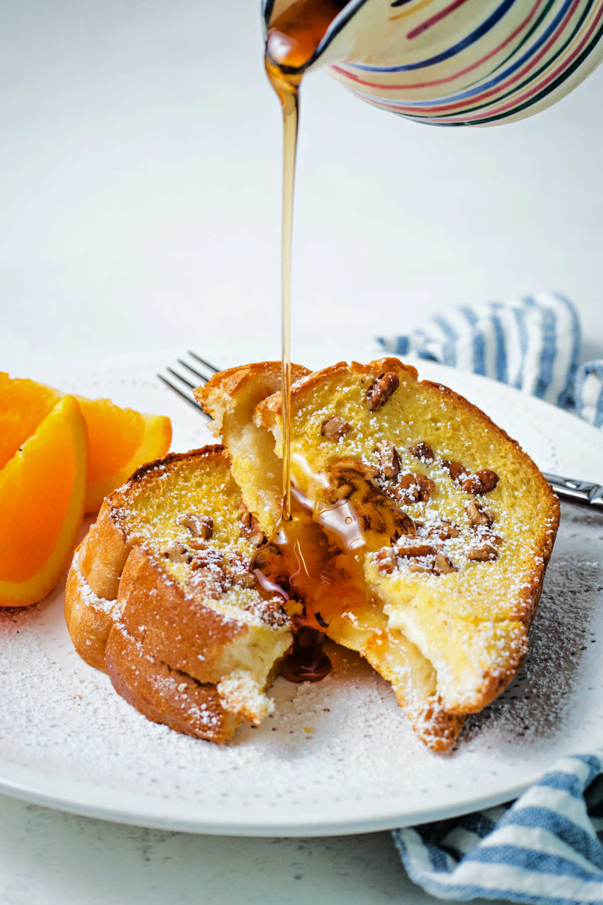 a stream of maple syrup being poured over slices of orange french toast on a white plate sitting on a table.
