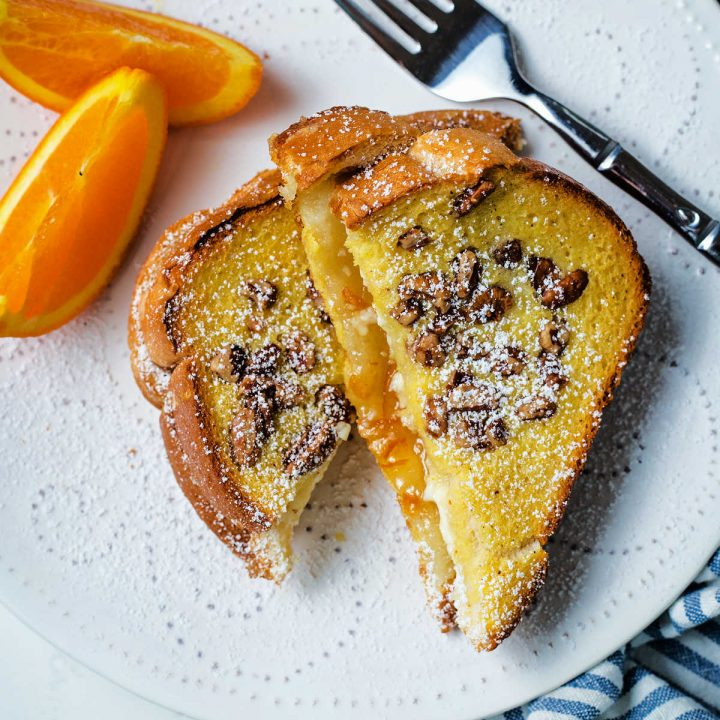 slices of orange french toast on a white plate with orange slices and sprinkled with powdered sugar.